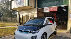white bmw I3 in front of 100% Tint Window Tint Company