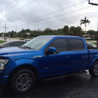 Blue Ford F150 with dark window tint done by 100% Tint